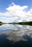 Lake in Norway with clouds reflection. Vertical view of a magnificent scenery in Norway, including the reflection of the sky on a lake Royalty Free Stock Image