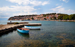 Lake in ohrid. Two boats by a quay, old town of Ohrid at the backgroud Royalty Free Stock Photo