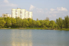 Lake outside the city in spring. Landscape of blue lake, trees and bushes with light-green leaf and buildings on background outside the city in spring stock photos