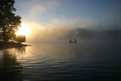 Lake of the Ozarks bass fishing sunrise. Two bass fisherman casting in the foggy fall sunrise Royalty Free Stock Photo