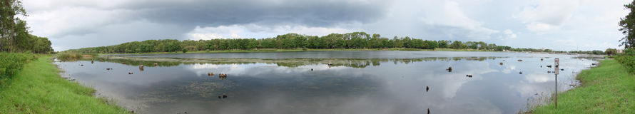 Lake in panorama. A panoramic shot of a lake and the banks. Overcast sky stock photography