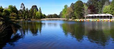 Lake Panorama. Panorama of a lake, with boathouse, paddleboats, and an arching bridge.  Glorious spring sunshine Royalty Free Stock Photos