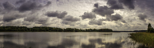 Lake panorama with clouds. Beautiful view of the lake with colorful clouds. Huge panorama of late summer Stock Images