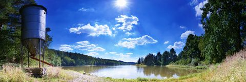 Lake Panorama at Noon. With sun, clouds and forest stock image