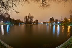 A lake in a park at night with lights and their reflections and apartment buildings.  Royalty Free Stock Photo
