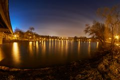 A lake in a park at night with lights and their reflections and apartment buildings.  Royalty Free Stock Photography
