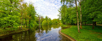 Lake in park panorama with green trees and blue water. Lake panorama with green trees around and blue water Royalty Free Stock Photography