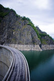 Lake and partial view of dam. A road leading over a dam, with views of the mountains, lake, and nature Stock Photo
