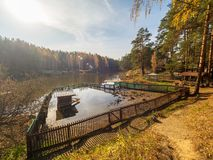 Lake with a pen for ducks, surrounded by autumn forest stock image