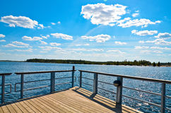 Lake pier against the blue sky Royalty Free Stock Photography