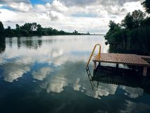 Lake Pier with sky and clouds reflecting in tranquil River. Lake Pier with blue sky and clouds reflecting in tranquil River Stock Photo