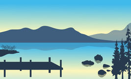 Lake and pier scenery. With mountain of silhouette Royalty Free Stock Photos