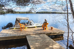 Lake pier with senior woman on chair and looking far away Royalty Free Stock Images