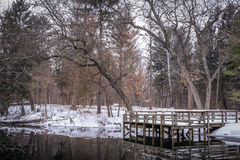 Lake pier in winter on a small pond in Wisconsin Stock Images
