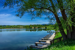 Lake with piers. Trees and blue sky in the background Stock Image