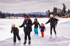 Girls Ice Skating on Mirror Lake. Lake Placid, NY / USA / March 3, 2016:  Young girls and instructor ice skating outdoors on frozen Mirror Lake during annual Stock Image