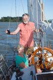 On the Lake. Portrait of a happy retired couple on their classic ketch on a lake under sunny skies stock image