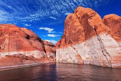 Lake Powell is surrounded by magnificent red hills. Walk on the boat at sunset. Scenic huge artificial water basin of the stock photography