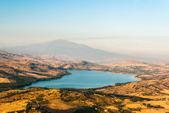 The lake of Pozzillo, with volcano Etna in background. The lake of Pozzillo, in Sicily, with volcano Etna in background; the town in the right shore of the lake Royalty Free Stock Photography
