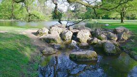 Lake in the public park close to Baden-Baden, Rastatt, water runs in a small waterfall in  brook. Lake in the public park close to Baden-Baden, Rastatt, water stock video footage