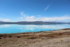 Lake Pukaki beautiful inverted reflection in water. You can see cloud and bule sky in the water royalty free stock photo