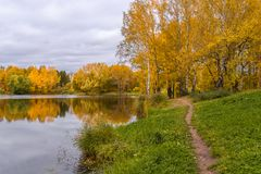 A lake reflecting the cloudy sky, trees with autumn leaves and a path along the shore Royalty Free Stock Photo