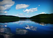 Lake Reflection. A beautiful calm day on the Ottawa River with a few white fluffy clouds in the blue sky reflecting on the glassy waters royalty free stock images
