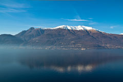 Lake reflection panorama on a sunny day. A view of Como Lake, Italy Royalty Free Stock Photo