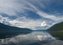 Panorama of a mountain lake with reflection of the sky and white clouds in calm water Royalty Free Stock Photography