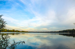 Landscape large clear lake with reflection of the sky and the forest Stock Image
