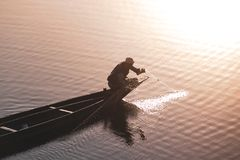 Lake with reflection of the sun and a person fishing from a boat stock image