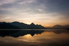 Lake Reflection at Sunrise. Lake reflection on a beautiful summer day, at sunrise in the Swiss Alps. Buochs, Switzerland royalty free stock image