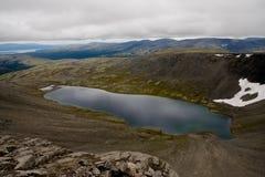 Lake reflects the clouds. Akademicheskoe lake behind the Polar Circle. Khibini mountains, Russia Royalty Free Stock Photos