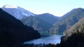 Lake Ritsa and the Caucasus mountains in Abkhazia. Natural landscape. View of the lake Ritsa. Trees reflecting in the water. Ritsa National Park, Abkhazia stock footage