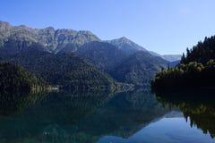 Lake Ritsa surrounded with high caucasus mountains mirroring in water Royalty Free Stock Photos