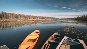Lake or river and old rowing fishing boats in beautiful autumn sunny day. Lake or river and old wooden rowing fishing boats in beautiful autumn sunny day stock footage