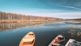Lake or river and old rowing fishing boats in beautiful autumn sunny day. Lake or river and old wooden rowing fishing boats in beautiful autumn sunny day stock video