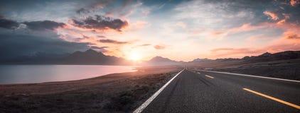 Lake and road at sunset royalty free stock image