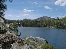 Lake with rocks. Alpine lake and pine forest framed by rocks Stock Photo