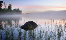 Lake. With rocks and reeds in the foreground Stock Photography
