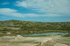 Lake on rocky landscape with domes of an old radar station. Lake over rocky landscape with bushes and domes of an old radar station on the highlands, at the royalty free stock photography