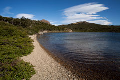 Lake in rocky shores and woods. Stock Images