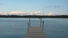 Lake scene with dock, fishing pole and fishing boat