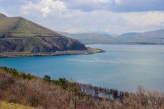 Free Lake Sevan Is The Largest Body Of Water In Armenia And In The Caucasus Region. Blue Expanses Of Water, Mountains And Meadow With F Royalty Free Stock Photography - 147004847