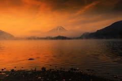 Lake Shoji and Mount Fujisan at sunrise. Mount Fujisan or Fuji with twilight sky at sunrise against heavy mist above Lake Shoji or Shojiko with orange light royalty free stock image