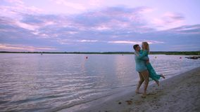 On the lake shore, a couple in love embraces and kisses. The man picks up and rotates the heel on his hands. On the lake shore, a couple in love embraces and stock footage