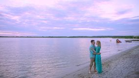 On the lake shore, a couple in love embraces and kisses. The man picks up and rotates the heel on his hands. On the lake shore, a couple in love embraces and stock video