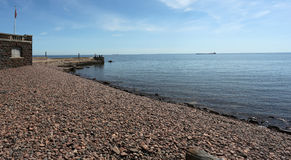 Lake Superior ship passing by a rocky shoreline  Royalty Free Stock Image
