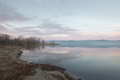 A lake shore at dusk Stock Images