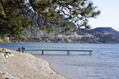 Lake Shore Family. A mother and her small kids and dog sit on a distant dock enjoying the peacful morning view in this landscape shot of Lake Okanagan by Royalty Free Stock Photos